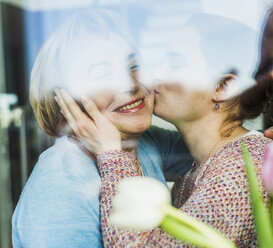 Young woman kissing senior woman behind windowpane - UUF006453