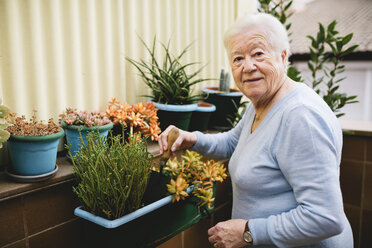 Portrait of senior woman gardening on her balcony - GEMF000680