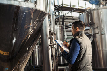Young man working in craft brewery - ZEDF000038