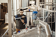 Young man working in craft brewery - ZEDF000044