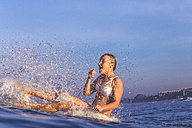 Indonesia, Bali, woman sitting on her surfboard splashing with water - KNTF000233
