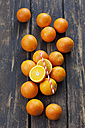 Whole and sliced oranges and a drinking straw on wood - CSF027022