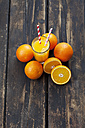 Whole and sliced oranges and glass of orange juice on wood - CSF027025