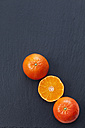 Whole and sliced tangerines on slate - CSF027061