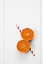 Two halves of a tangerine and a drinking straw on white ground - CSF027064