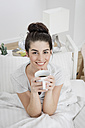 Portrait of smiling young woman with cup of coffee in bed - GDF000964