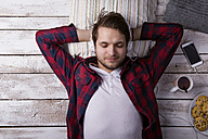 Portrait of young man lying on the floor listening music with headphones - HAPF000182