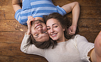 Portrait of young couple in love lying head to head on wooden floor - HAPF000194
