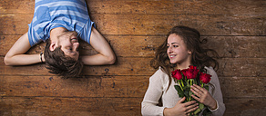 Young couple in love lying on wooden floor - HAPF000197