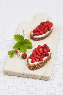 Slices of bread with cream cheese and woodland strawberries on chopping board - GWF004600
