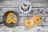 Pancakes with blueberries on plate, chopping board and pan - LVF004496