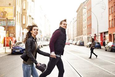 Germany, Berlin, happy couple crossing a street - GCF000125