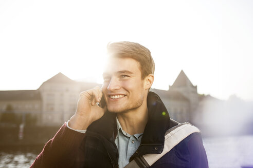 Germany, Berlin, young man on the phone at River Spree - GCF000164