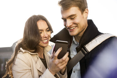 Smiling young couple looking at smartphone outdoors - GCF000170