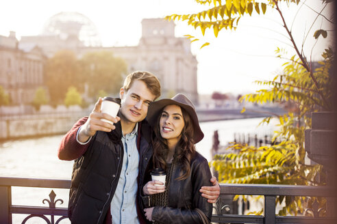 Germany, Berlin, young couple at River Spree with coffee to go - GCF000173