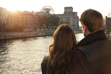 Germany, Berlin, young couple at River Spree looking at Reichstag - GCF000179