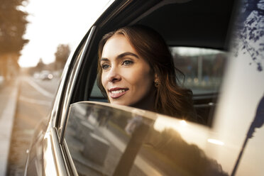 Smiling young woman looking out of car window - GCF000182