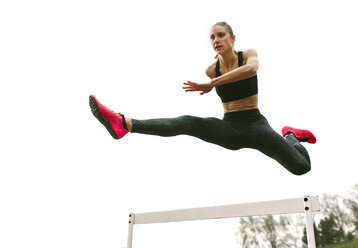 Athlete woman jumping in a running track - MGOF001320