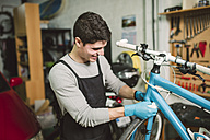 Mechanic repairing a bicycle in his workshop - RAEF000824
