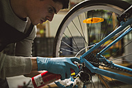 Mechanic oiling a bike chain - RAEF000827