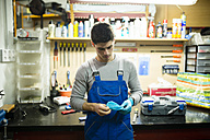 Mechanic in his workshop putting on working gloves - RAEF000833