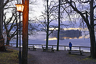Germany, Bavaria, Lake Staffelsee, senior woman at lakeshore at dusk - LAF001604