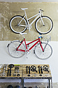 Two custom-made bicycles hanging on the wall in a store - JUBF000095