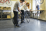 Salesman advising client in a custom-made bicycle store - JUBF000098