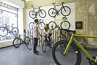 Client testing racing cycle in a custom-made bicycle store - JUBF000104