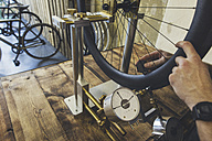 Mechanic working on tire in a custom-made bicycle store - JUBF000107