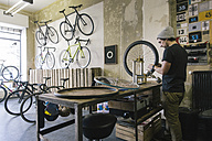 Mechanic working on tire in a custom-made bicycle store - JUBF000110
