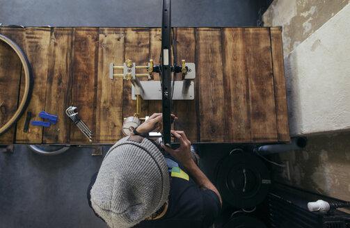 Mechanic working on bicycle tire - JUBF000113