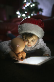 Portrait of little girl wearing Christmas cap using digital tablet at home - MGOF001333
