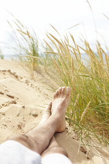 Sweden, Mellby, man lying barefoot on beach dune, partial view - TSFF000002