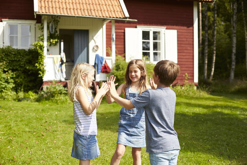 Sweden, three children playing on a meadow in front of holiday home - TSFF000014