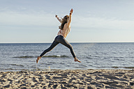 Spain, Lleida, woman jumping on the beach - JPF000110