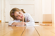 Portrait of smiling little girl lying on wooden floor with crayons and sheet of paper - LVF004509