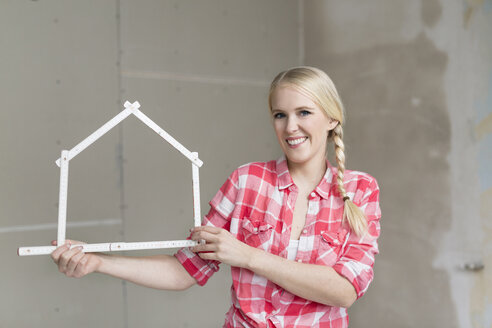 Smiling young woman holding pocket rule in shape of a house on construction site - SHKF000483