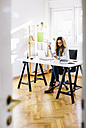 Young woman with cup of coffee and smartphone sitting at desk in her home office - AKNF000036