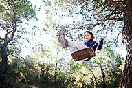 Spain, Siurana, little boy having fun on a swing in the forest - VABF000134