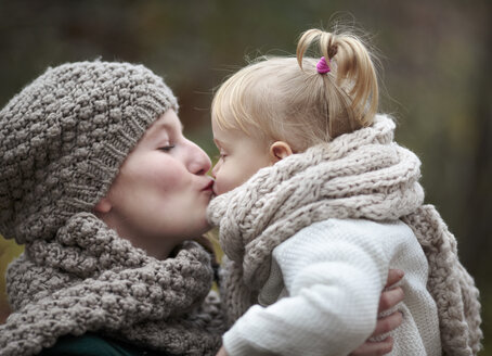 Young woman kissing her little daughter in autumn - NIF000070