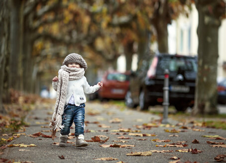Portrait of happy little girl wearing big scarf and woolly hat in autumn - NIF000073