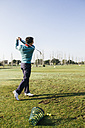 Golfer hitting a golf ball in the driving range of a golf club - ABZF000184