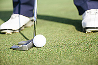 Close up of a golfer ready to hit a golf ball on the green of a golf course - ABZF000187