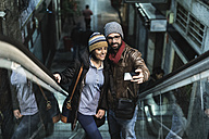 Couple on escalator taking a selfie - JASF000371