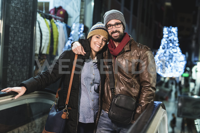 Couple on escalator with shops and night lights in background - JASF000374 - Jaen Stock/Westend61