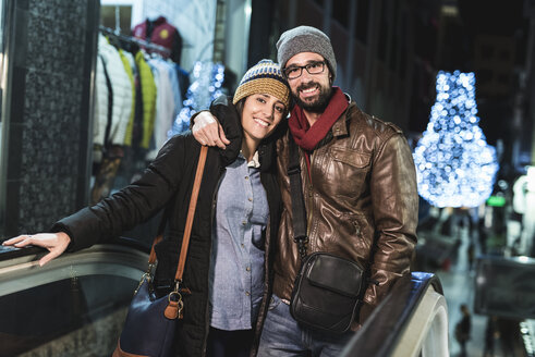Couple on escalator with shops and night lights in background - JASF000374