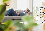 Young man lying on the couch using laptop - UUF006484