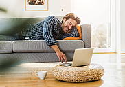 Young man lying on the couch at home looking at laptop - UUF006490
