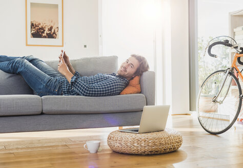 Young man with digital tablet lying on the couch at home - UUF006493